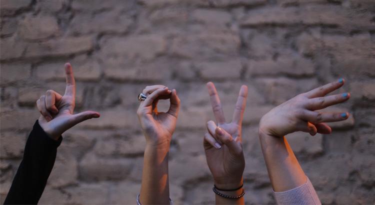 Vier Hände, die die Buchstaben L o v e formen.