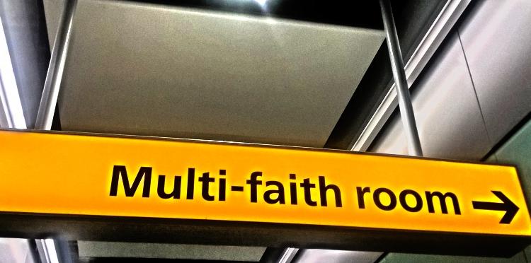 Hier ist ein gelbes Schild zu sehen. Darauf steht: Multi-faith room. Raum für verschiedene Religionen.