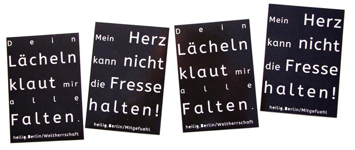 """Zwei Sorten von schwarze Aufklebern sind auf dem Bild zu sehen. Auf der einen Sorte steht: """"Mein Herz kann nicht die Fresse halten. heilig.berlin/mitgefuehl"""" Auf den anderen steht: """"Dein Lächeln klaut mir alle Falten. heilig.berlin/weltherrschaft"""" Foto: Stephan Hartmann"""
