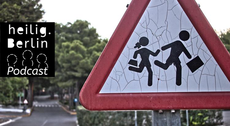 Dreieckiges Straßenschild mit roter Umrandung. In der Mitte Mädchen und Junge oder junge Frau und junger Mann, die nach rechts, rennen. Im Hintergrund Bäume und Straße. Zudem ist das Logo von heilig.Berlin zu erkennen.