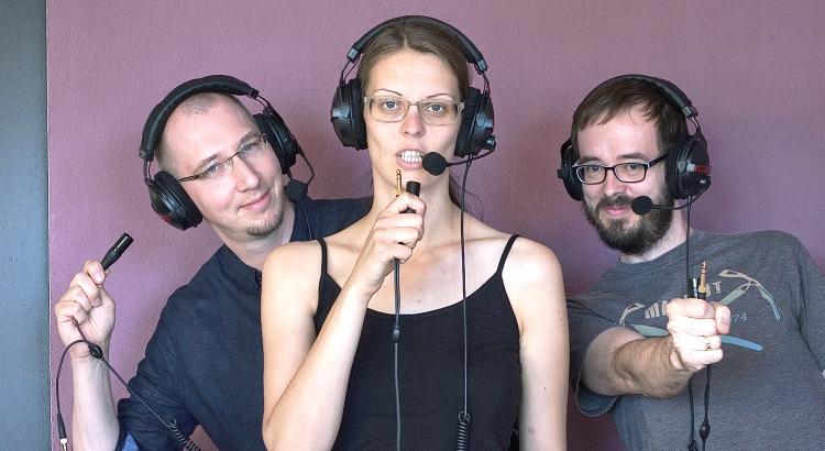 Das heilig.Berlin Podcast Team: Dietmar, Jana, Stephan. Sie schauen in die Kamera, haben Kopfhörer auf und halten die Kopfhörerstecker fest.