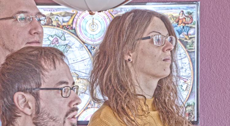 Beitragsbild zur Folge mit dem Thema Weltherrschaft. Drei Personen schauen rechts aus dem Bild. Hinter ihnen einen Weltkarte.