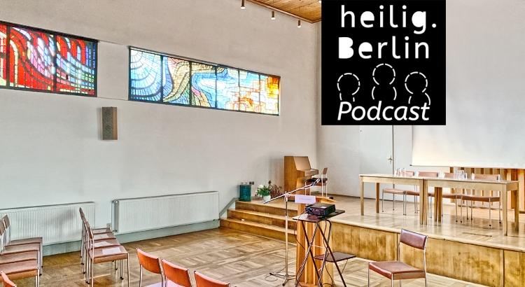 """Gemeindesaal mit Buntglasfenstern und leeren Stühlen und Tischen. Im Vordergrund """"heilig.Berlin Podcast"""" Logo. Foto: Stephan Hartmann"""