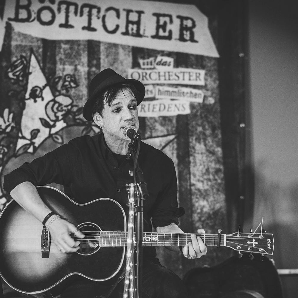 Jens Böttcher mit Gitarre in den Händen und Mikrofon vor dem Mund.